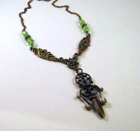 Antiqued bronze sword necklace jewelry with green teardrop beads